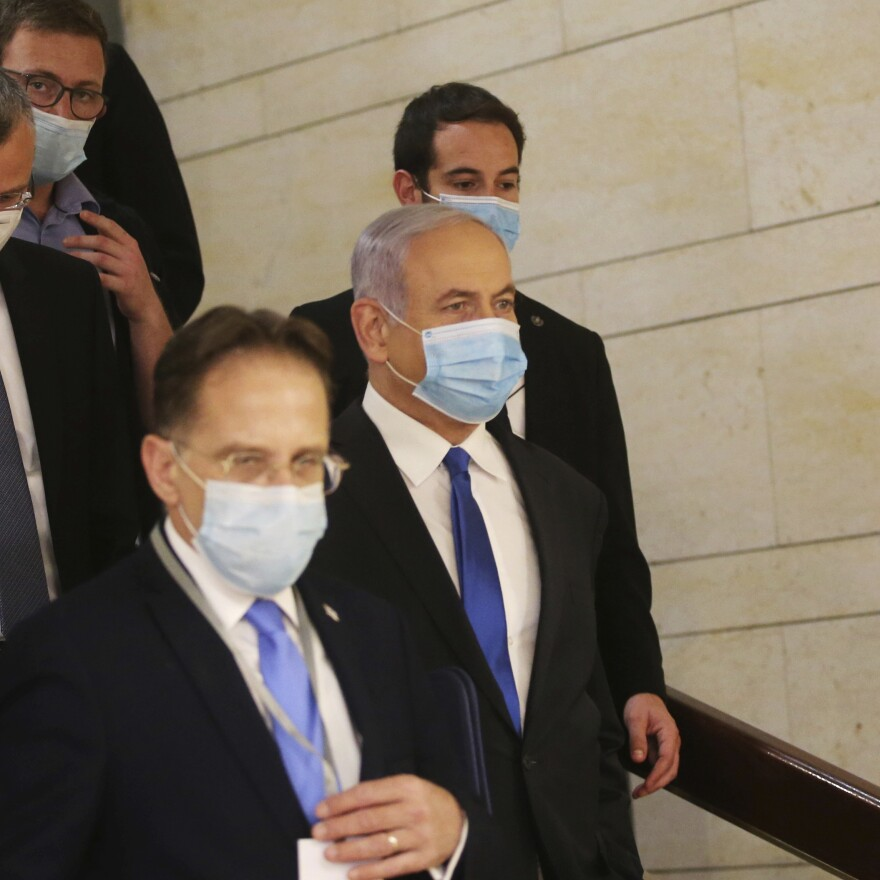Israeli Prime Minister Benjamin Netanyahu (center) wears a protective face mask as he makes his way to attend the swearing-in ceremony of his new government, at the Knesset, Israel's parliament, in May. The Knesset has dissolved and Israel is headed to new elections for the fourth time in two years.