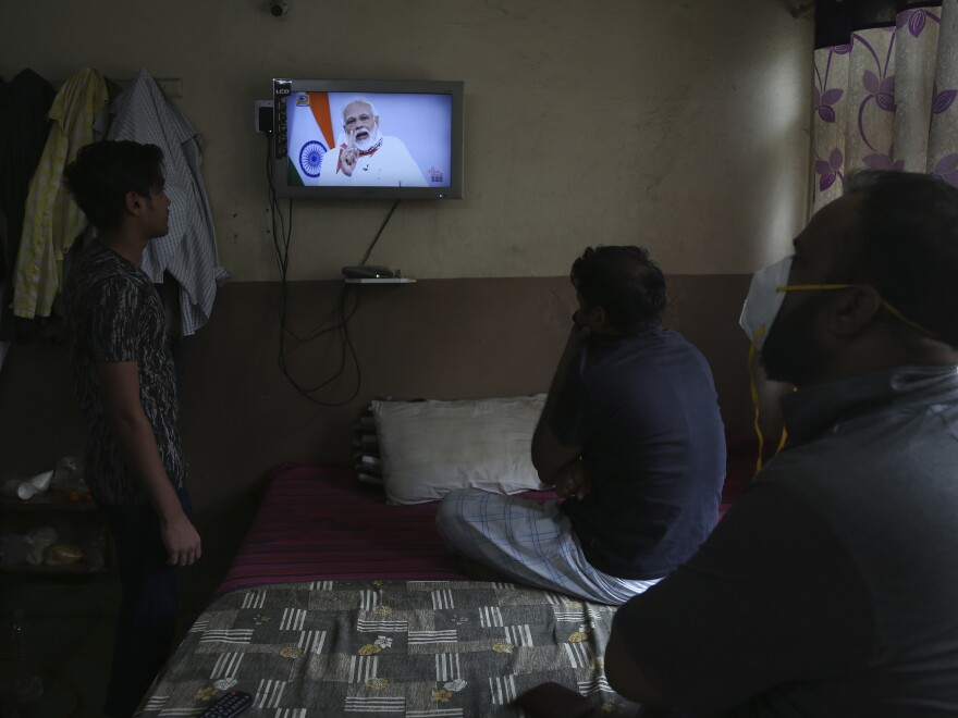 People in Hyderabad, India, watch Prime Minister Narendra Modi address the nation Tuesday. Modi has extended the world's largest coronavirus lockdown in hopes of reducing the epidemic's peak.