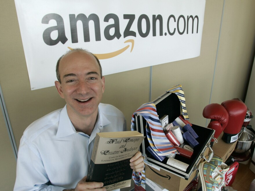 """Amazon.com founder and CEO Jeff Bezos holds a copy of """"Fluid Concepts and Creative Analogies"""" by Douglas Hofstadter, the first book sold on-line by Amazon.com in 2005. The company is trying to prevent California from charging tax on purchases made on the companies website."""