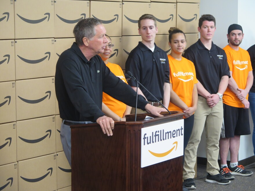 A photo of Gov. Kasich speaking at an Amazon facility.
