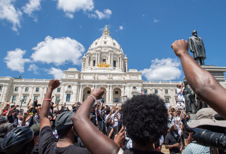 Supporters raise their fists while standing at the State Capitol during a National Mother's March in St. Paul, Minnesota July 12, 2020. (Amanda Sabga/AFP via Getty Images)