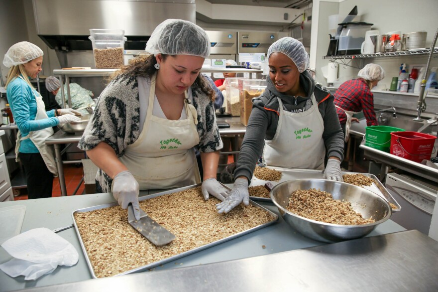 Jenyka Gassnola, an intern, and Hanna Teklu, a graduate of the program and now a program assistant, smooth out the granola before it goes to the oven to bake.