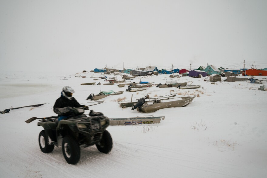A person on an all-terrain vehicle drives past boats at the edge of Toksook Bay. During winter, census workers are able to journey across miles of frozen ground and ice roads to reach villages usually accessible only by plane or boat in the warmer months.
