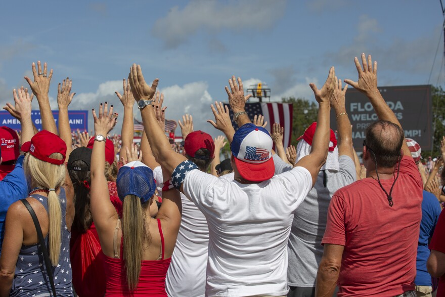 people at political rally waving hands in air