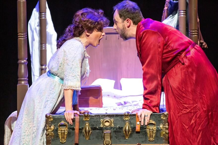 A man and a woman face each other on stage, on either end of a green and gold trunk, with a four-poster bed in the background
