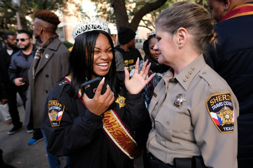 Huston-Tillotson Parade Queen Kiera Percy reacts after Sheriff Sally Hernandez lends her her jacket