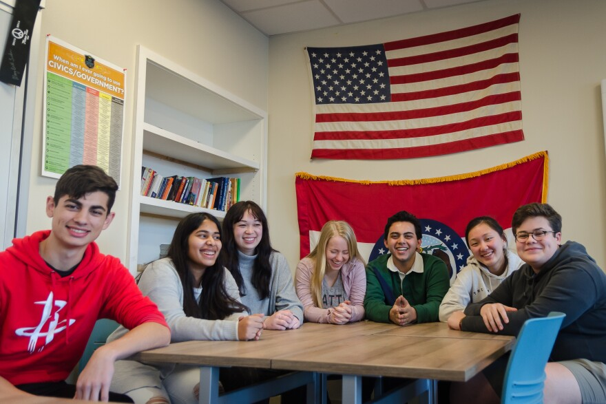 Seven of the 21 Clayton High School students who will soon travel to Iowa to take part in the presidential races try to pose for a group photo. Jan. 8, 2020
