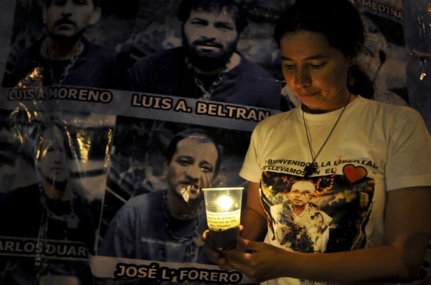 Miriam Lasso, sister of police sergeant Cesar Augusto Lasso who was kidnapped by the FARC in Nov. of 1998, holds a candle next to pictures of several police and military hostages of the FARC, in January in Cali.