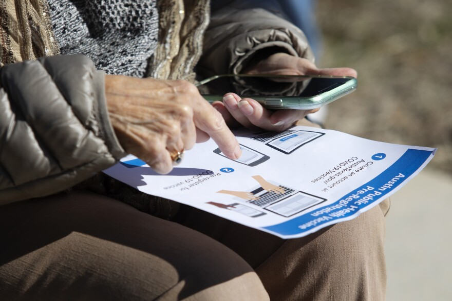 A person looks at instructions on how to register for a vaccine through Austin Public Health.