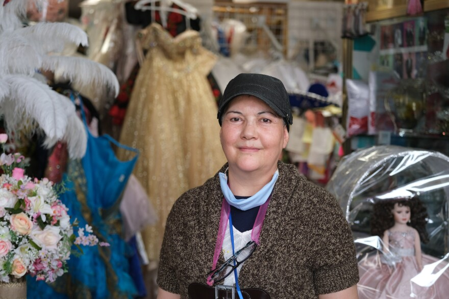 Picture of a women wearing a black hat standing in a shop full of quincenera dresses
