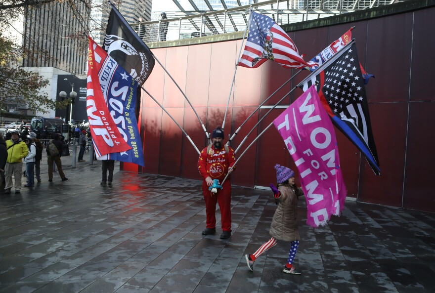 An attendee displays flags during the rally held by the Washington Three Percent in Seattle last month.