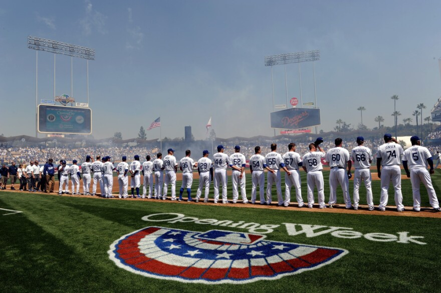 The L.A. Dodgers stand on the third baseline during the national anthem on opening day at Dodger Stadium. They beat the Pittsburgh Pirates, 2-1, on Tuesday in Los Angeles.