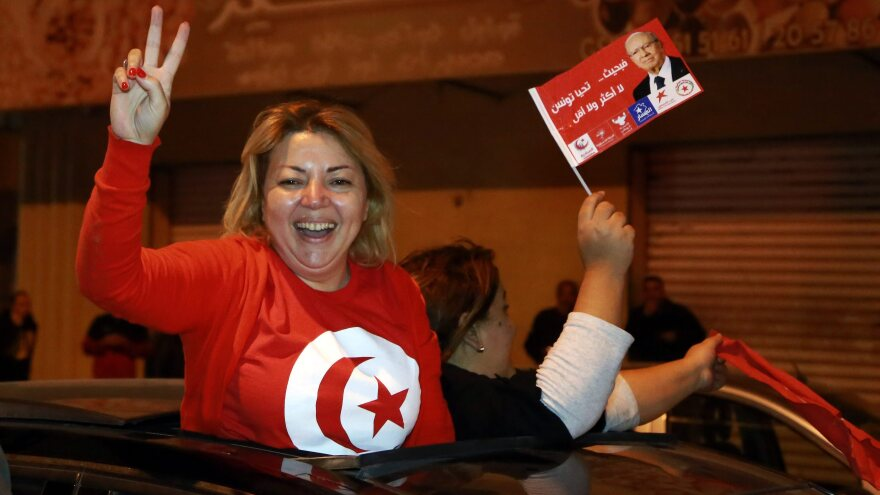 A supporter of newly elected Tunisian presidential candidate Beji Caid Essibsi flashes the V-sign from a car as they celebrate the first results of the Tunisian elections in Sousse, Tunisia.