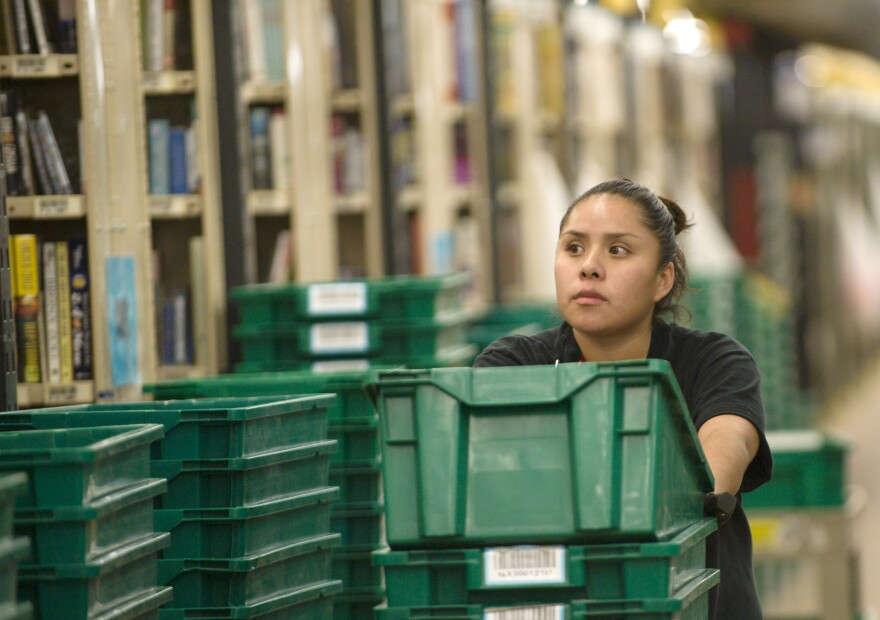 An Amazon.com employee gathers books for shipping at a warehouse in Fernley, Nev., in December 2008.