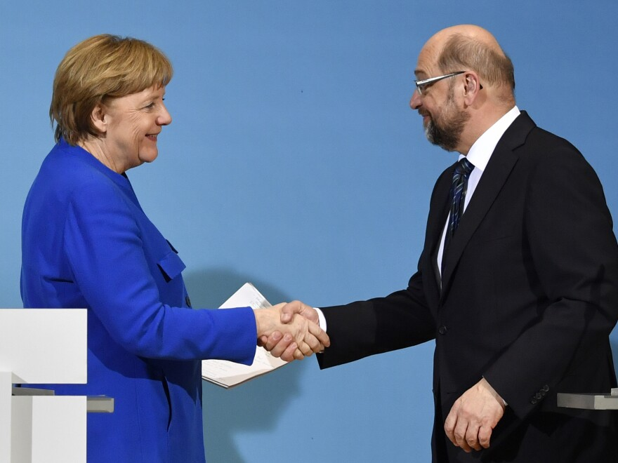 "German Chancellor Angela Merkel shakes hands Friday with the leader of the Social Democratic Party, Martin Schulz. Merkel's conservatives reached a ""breakthrough"" deal with the Social Democrats toward building a new coalition government, sources close to the negotiations said."