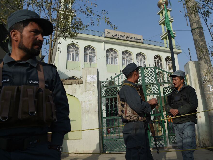 Afghan policemen stand guard outside the Imam Zaman Shiite mosque the day after a suicide attack during Friday evening prayers last October.