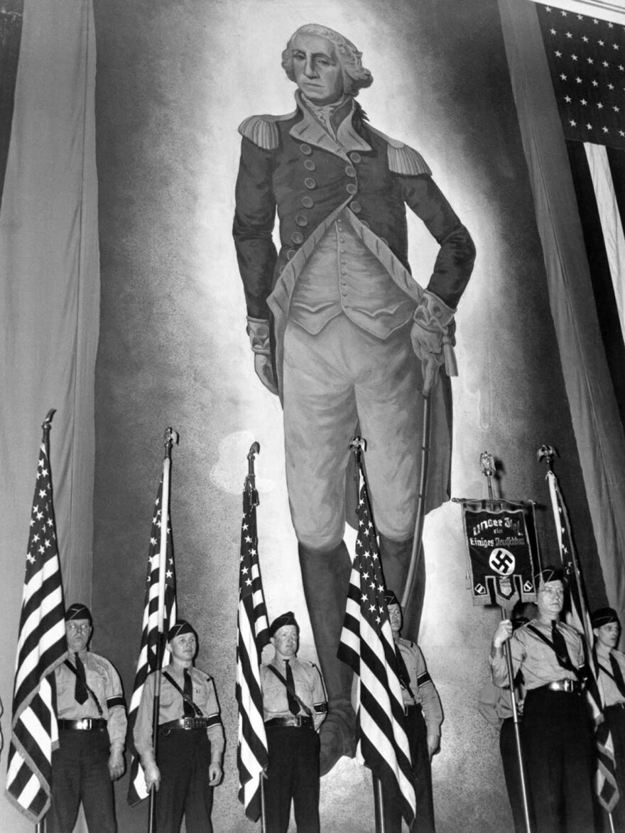 A color guard holding American flags and a banner inscribed with the Nazi swastika stands before an immense portrait of George Washington at the German American Bund's rally at Madison Square Garden.