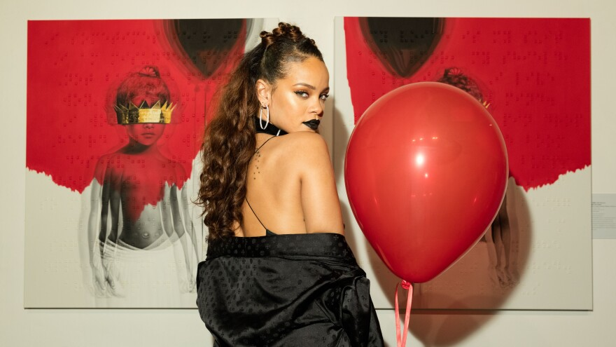 Rihanna in October 2015, in front of the cover art for her album, <em>Anti.</em>