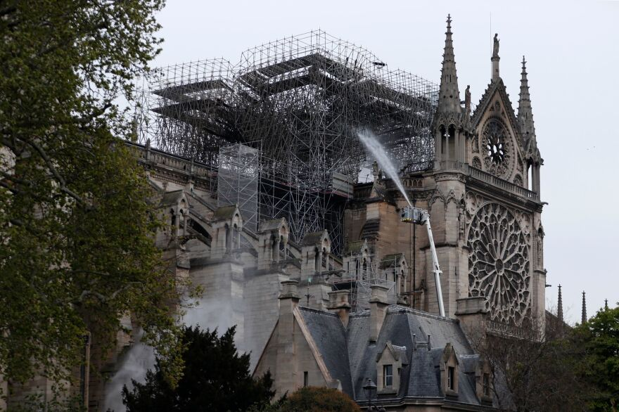 "Firefighters spray water as they work to extinguish a fire at Notre Dame Cathedral in Paris early on Tuesday. A huge fire that devastated Notre Dame Cathedral is ""under control"", the Paris fire brigade said after firefighters spent hours battling the flames."