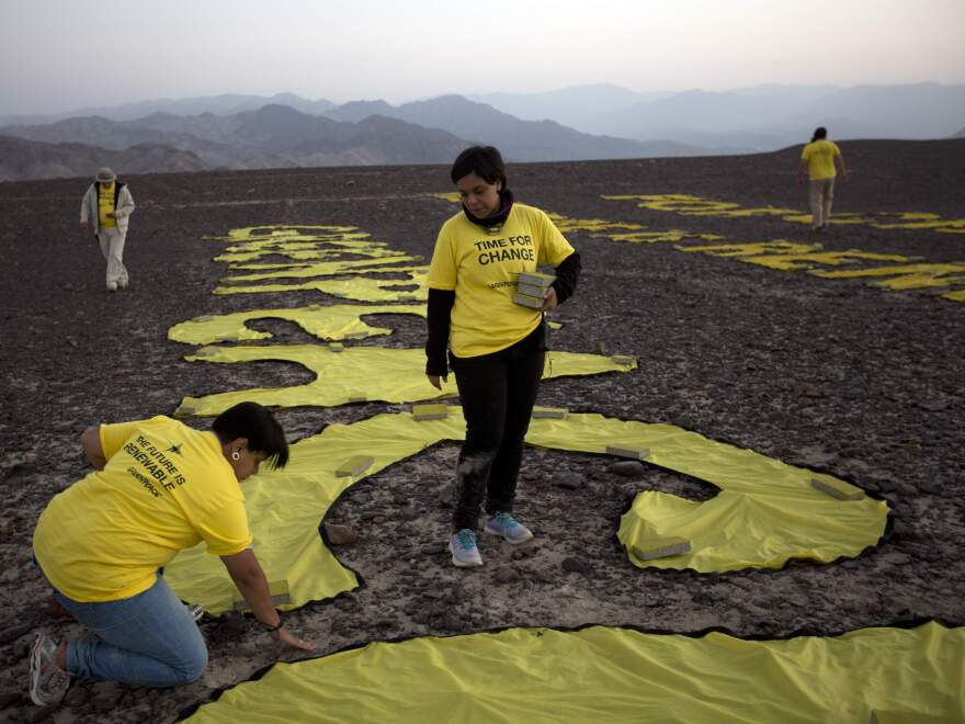 Greenpeace activists arrange the letters next to the hummingbird geoglyph in Nazca, Peru. Greenpeace apologized for the protest Wednesday, saying it came across as careless and crass.