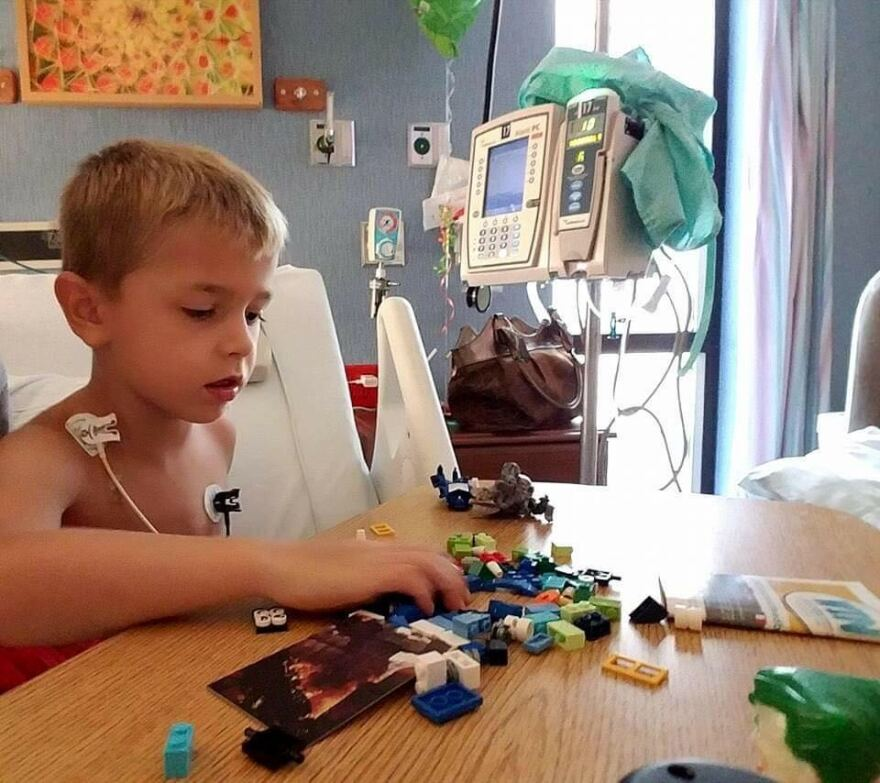 Seven-year-old Zyler Woodword plays with Legos while he receives his treatment for muscular dystrophy. He was one of more than 100,000 people who were dropped from the state's Medicaid rolls in the last 18 months.