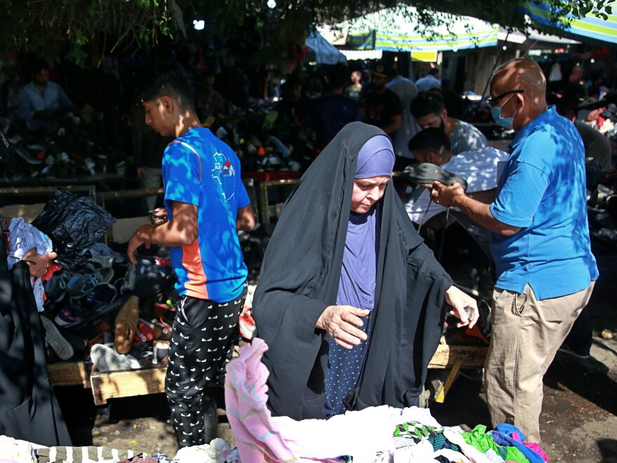 People shop in October for used clothes at the Baghdad market selling them.