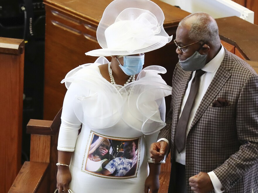 Tomika Miller, the widow of Rayshard Brooks, wears a white dress bearing a photograph of herself and her husband during his public viewing at Ebenezer Baptist Church on Monday.