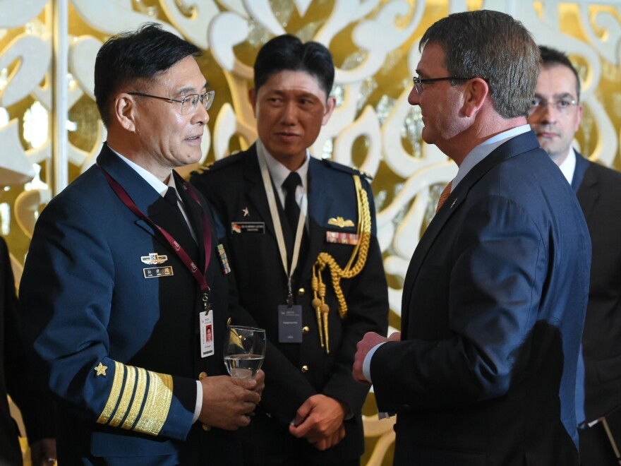 Sun Jianguo (left), from the Chinese People's Liberation Army Navy, chats with U.S. Secretary of Defense Ashton Carter in May during the ministerial luncheon at the 14th Asia Security Summit in Singapore. Each country has grown increasingly wary of the other's actions and interests in the South China Sea.