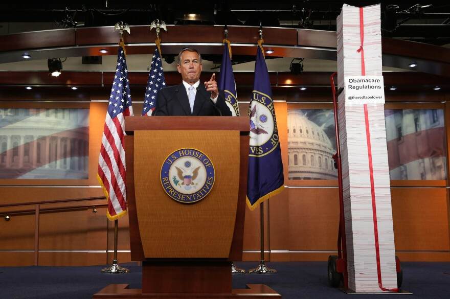 Then-Speaker of the House John Boehner stands next to a printed version of the Affordable Care Act during a Capitol Hill news conference on May 16, 2013.