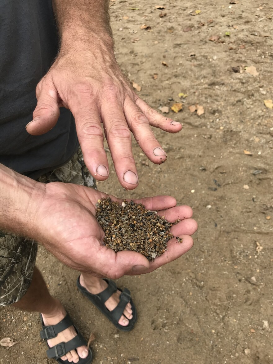 Bonne Terre resident Steven Anderson holds a handful of mine tailings from a beach in St. Francois State Park.