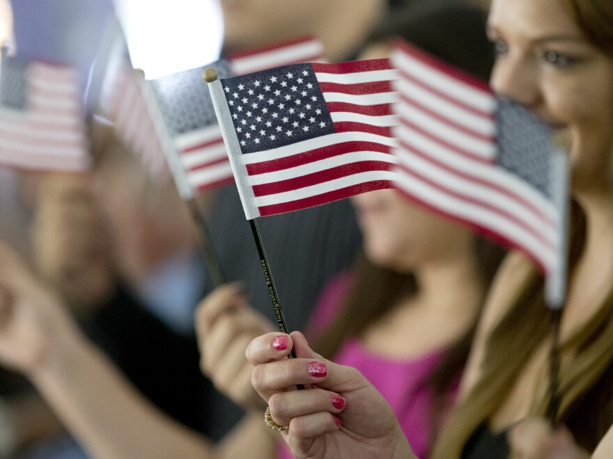 New citizens wave American flags during a U.S. Citizenship and Immigration Services naturalization ceremony  in Miami.