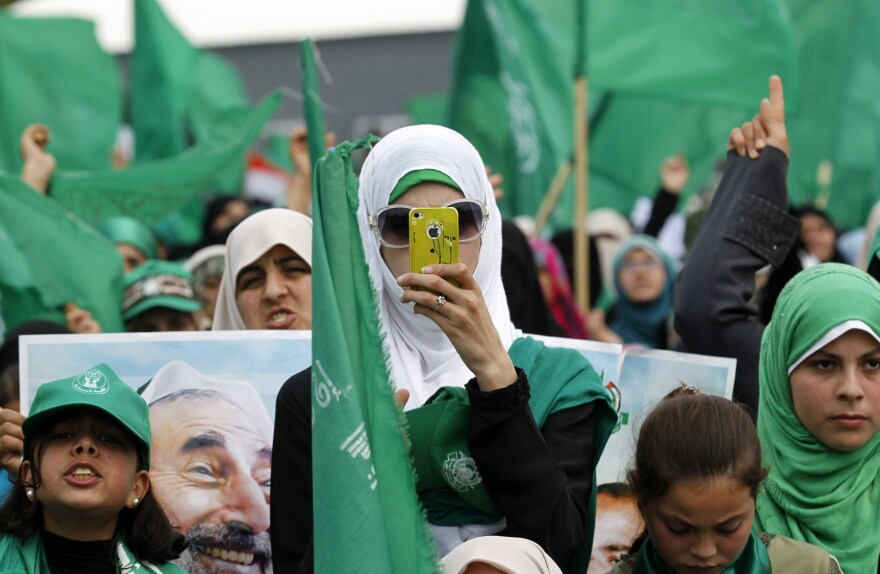 A Hamas supporter holds her mobile phone during a public rally in Gaza City in March.