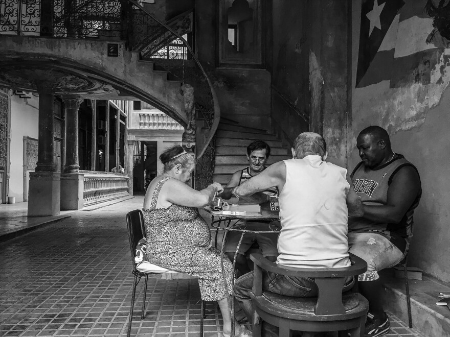 Four neighbors play dominoes at a residential building known as Solar de Aguilar in Havana, Cuba.