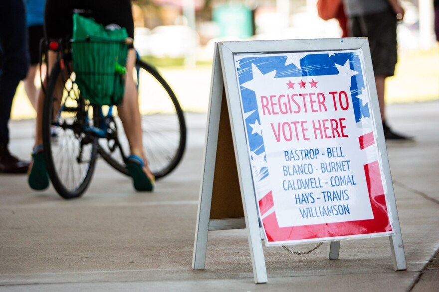 A sign tells people they can register to vote at a table outside the Palmer Events Center.