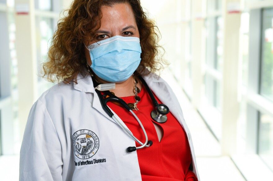 A doctor wearing a mask, white coat and stethoscope stands in a hospital hallway facing the camera.