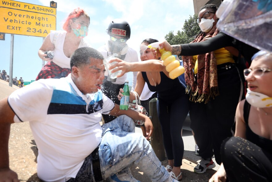 Protesters help a man pepper-sprayed by the police on the shoulder of Interstate 35.