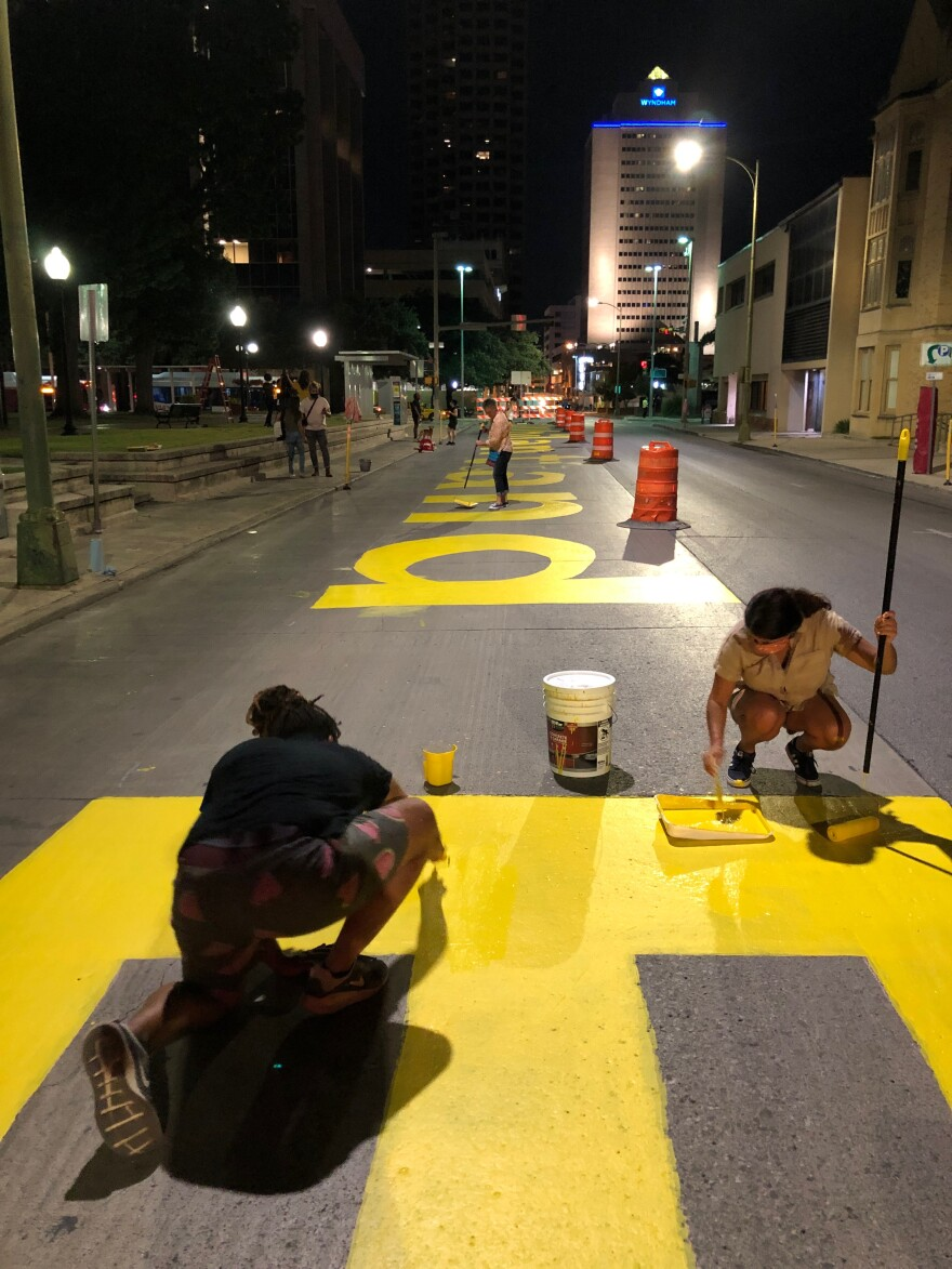 "Volunteers paint the words of a poem from San Antonio's poet laureate Andrea ""Vocab"" Sanderson on downtown city streets."