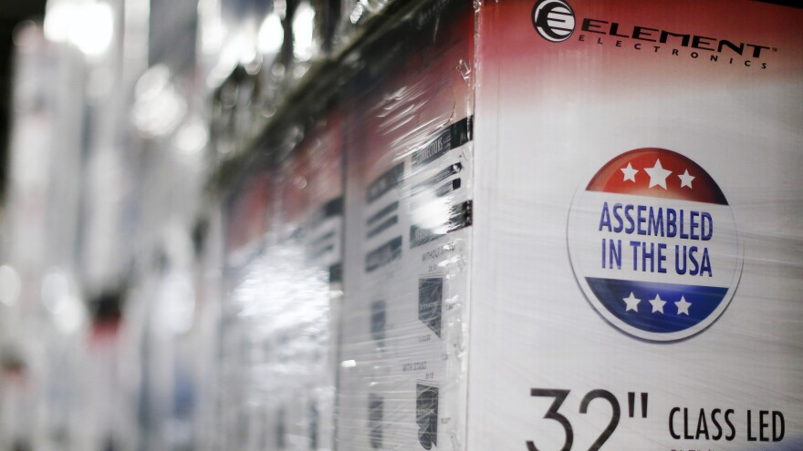 """An """"Assembled in the USA"""" stamp is seen at the side of a box containing a 32-inch television set May 29 in the warehouse of Element Electronics, in Winnsboro, S.C. For the phenomenon of """"reshoring,"""" or bringing overseas jobs back to the United States, the electronics sector has been a leader."""