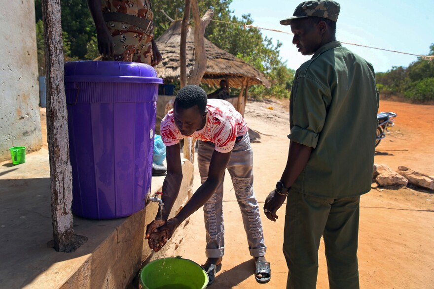 The new normal in Guinea is washing hands with a mixture of water and bleach--shown here at the border entrance of Buruntuma, in the Gabu area on Tuesday.