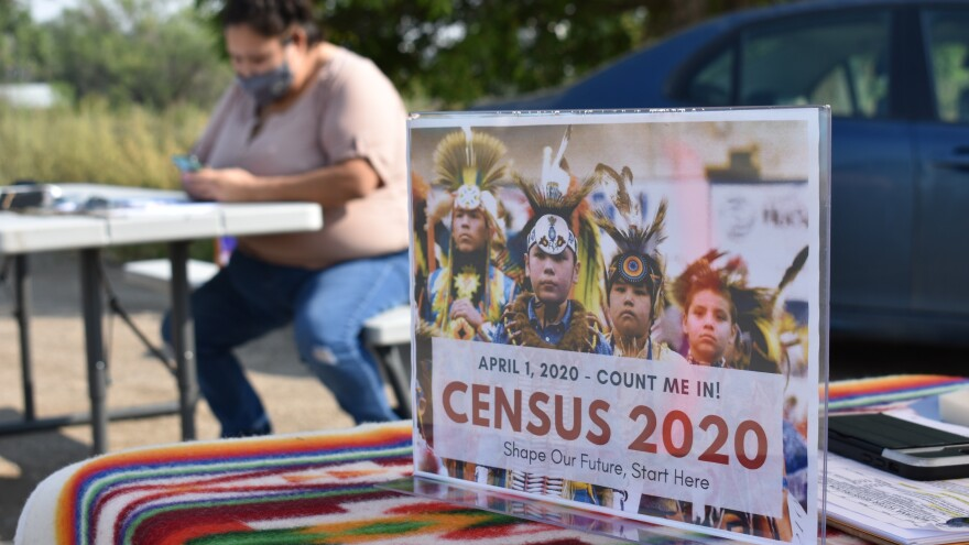 A sign promoting participation in the 2020 census is displayed nearby as Selena Rides Horse enters information into a phone for a member of the Crow Indian Tribe at a counting station set up by Western Native Voice in Lodge Grass, Mont., in August.