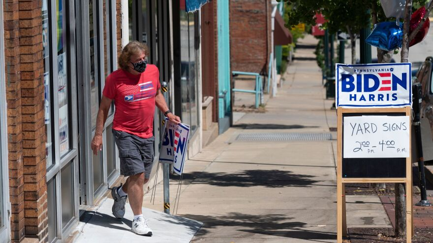 A man walks out of the Washington County Democratic Party office last week, in the suburbs of Pittsburgh, after taking a Joe Biden yard sign. Because of the coronavirus pandemic, Biden's campaign isn't doing any in-person door-knocking.