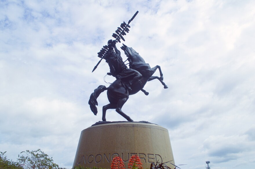 """A giant statue is shown depicting a Seminole man riding a horse. The man raises a long feathered spear high above his head. The horse stands on its back legs. The statue rests on a cylindrical platform with the words, """"unconquered"""" engraved on it. The sky is blanketed with clouds."""