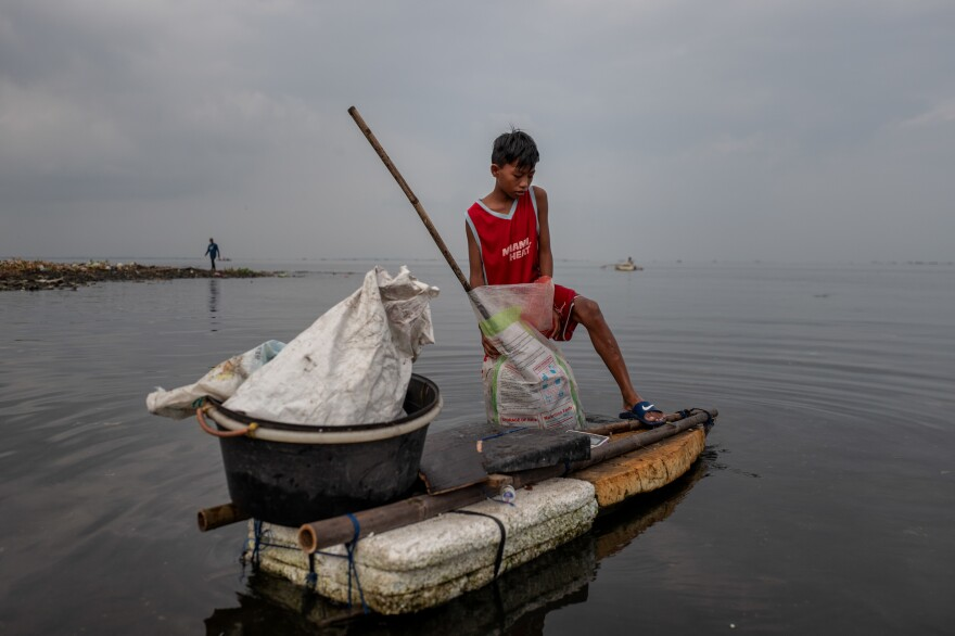 Children fill sacks with plastic trash from Manila Bay that they intend to sell to recyclers.