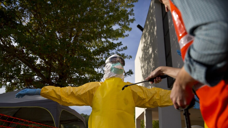 A licensed clinician is decontaminated before disrobing at the end of a simulated training session by CDC in Anniston, Ala. Training can take a several weeks, making some employers reluctant to encourage their medical workers to volunteer in the Ebola outbreak.