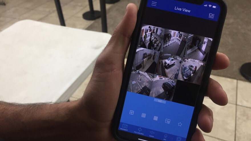 """Kamel Elwazeir looks at a surveillance app on his phone. """"It's truly sickening but it's part of our life,"""" Elwazeir says of having to implement security measures at his mosque. """"It's part of our society that we have to be prepared in case of an emergency."""""""
