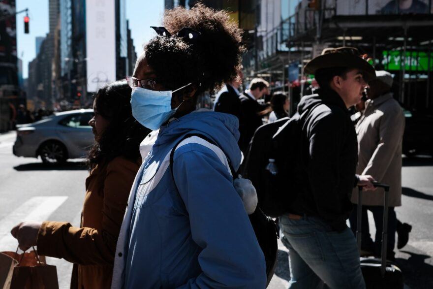 People walk through Manhattan with surgical masks as fears of the coronavirus spreading through the U.S. increase.