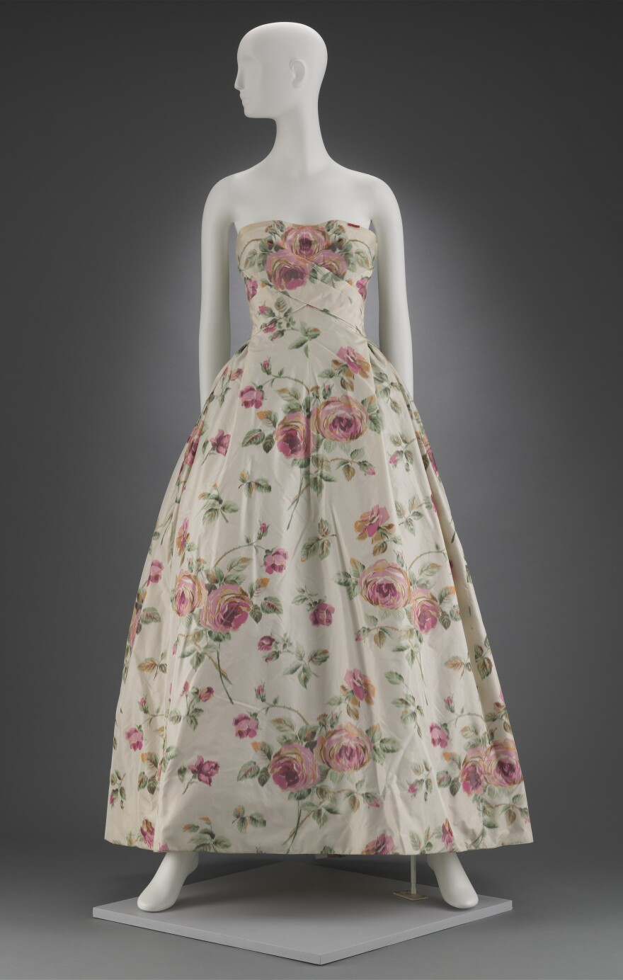 Big, pink flowers bloom on ivory silk in this 1956 dress by Christian Dior.