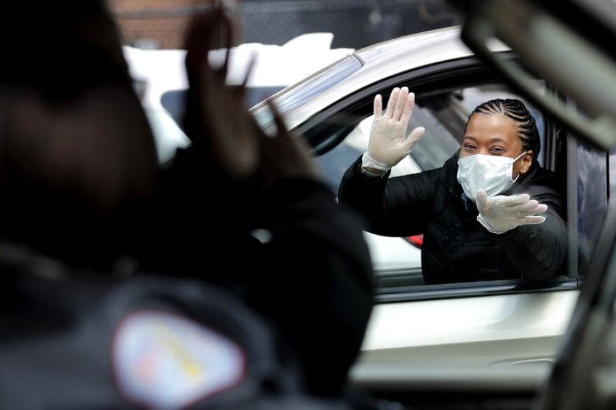 Chicago Police officer Cheryl Clark greets co-workers from her car while waiting to get PPE