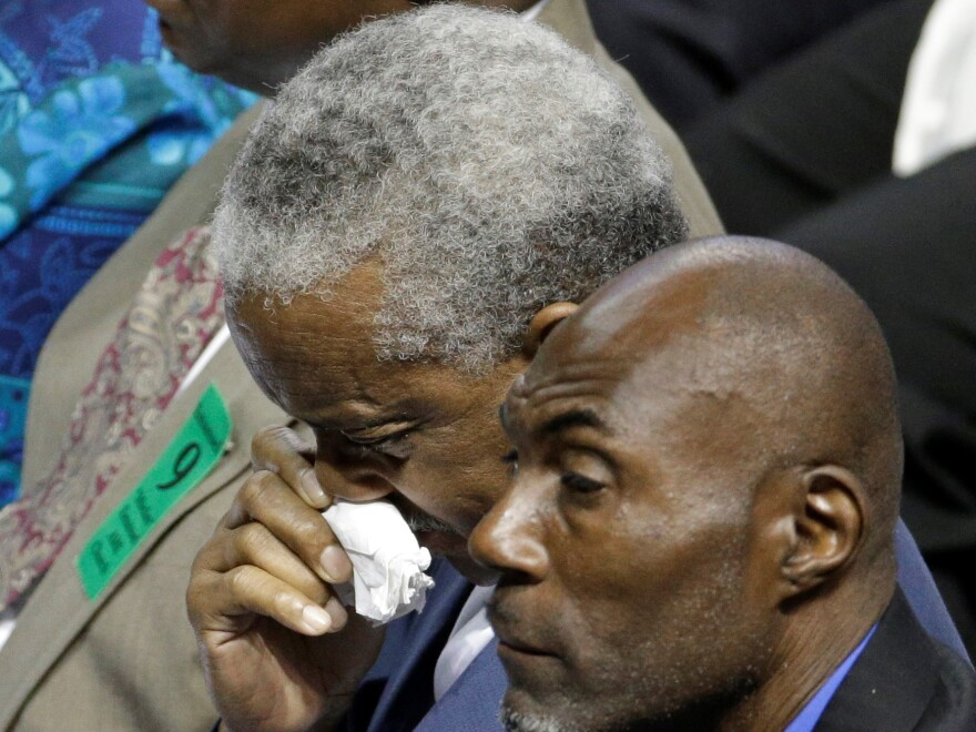 Rev. Anthony Thompson, background, husband of victim Myra Thompson, wipes his face during a memorial in Charleston, S.C., Friday, June 17, 2016 on the anniversary of the killing of nine black parishioners during bible study at Mother Emanuel AME Church.