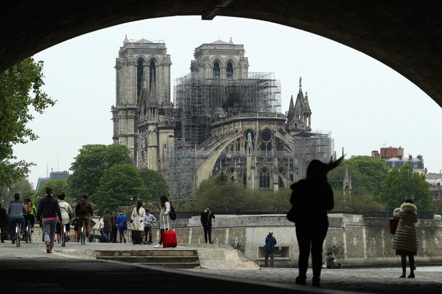 People look up at the damage caused to Notre Dame Cathedral on Tuesday in Paris. A fire broke out on Monday afternoon and quickly spread across the building, causing the famous spire to collapse.